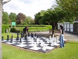 Two people playing giant chess in Gadebridge Park